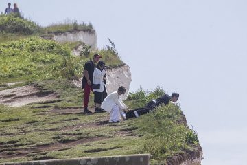 Tourists pose for photographs on edge of crumbling Birling Gap cliff on